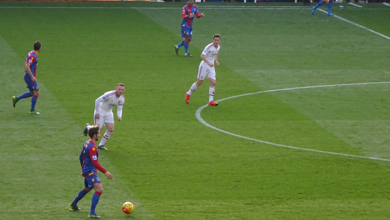 Palace's French playmaker Yohan Cabaye runs at the Man U goal area, closely watched by Wayne Rooney.