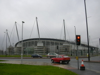 City of Manchester Stadium 2 [Note cars with hubcaps].JPG